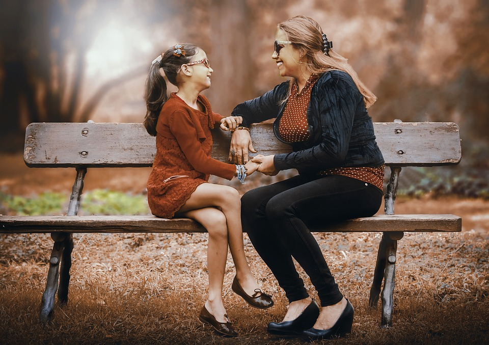 Mum and daughter chatting on a bench