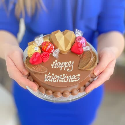 Woman holding a Valentines Day smash cake